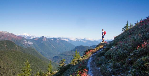 Homme dans la nature en montagne qui fait une randonnée pour échapper au quotidien de la ville