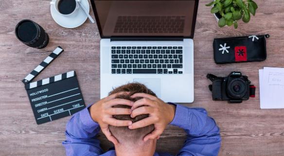 Homme qui réfléchit difficilement sur l'ordinateur posé sur le bureau avec des objets dont un café un appareil photo une plante un bloc note et un clap.