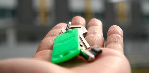Il y a une main de quelqu'un avec des clés de maison ou d'appartement dessus