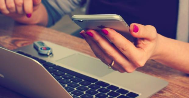 Il y a une femme avec un iphone et un ordinateur avec clé USB qui fait sa recherche immobilière