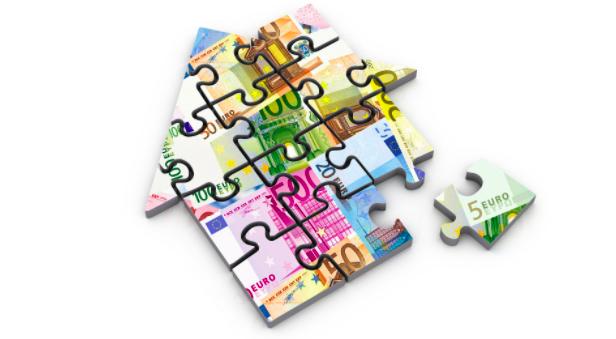 Puzzle d'une maison avec des billets de 10, 20, 100 et 200 euros