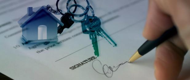 Une signature d'un acquéreur immobilier au compromis de vente de sa nouvelle maison dont il devient propriétaire.