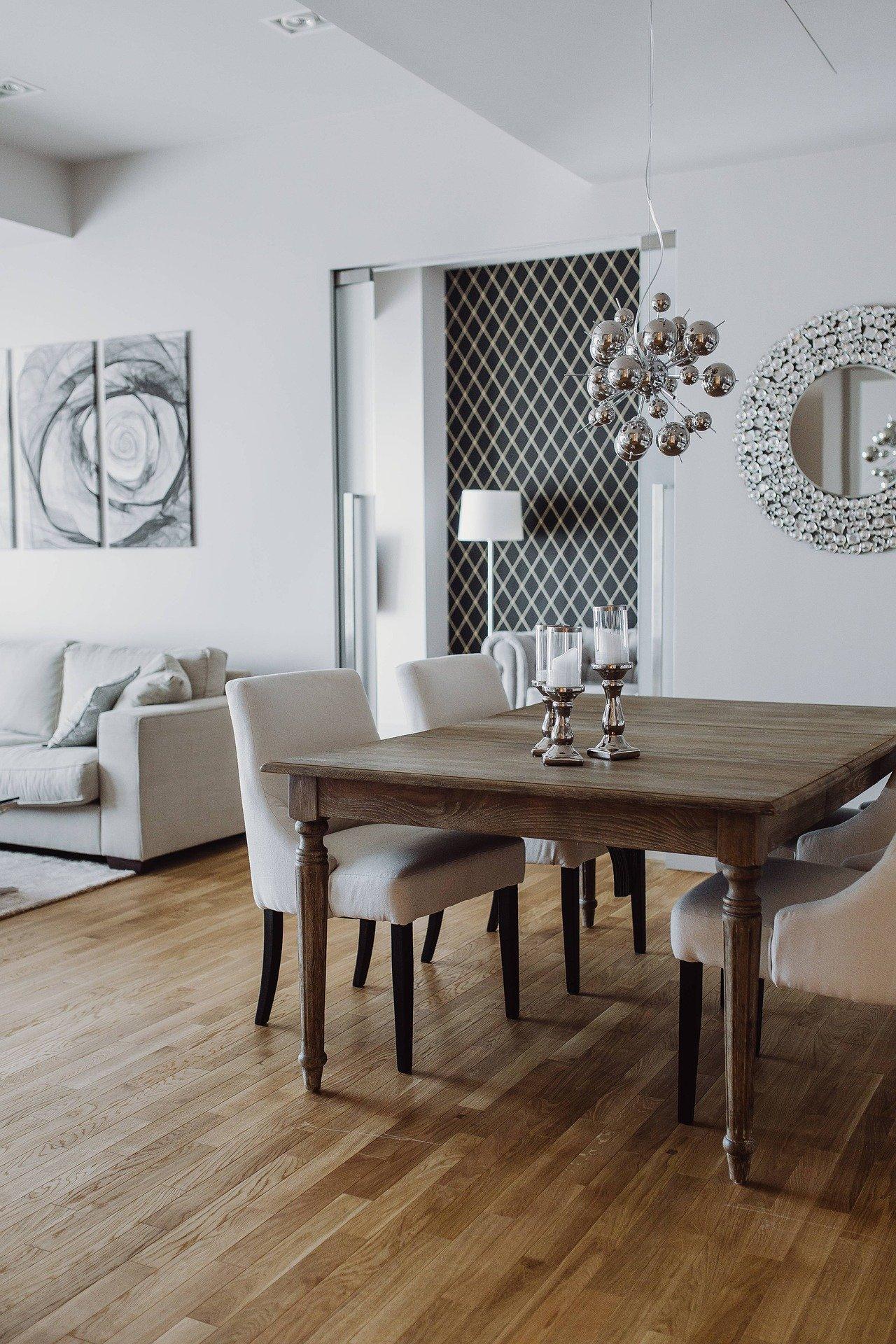 C'est un salon salle à manger avec une table en bois moderne et des chaises. On aperçoit un canapé et un tableau en arrière-plan. Une décoration immobilière digne d'un vrai home staging.